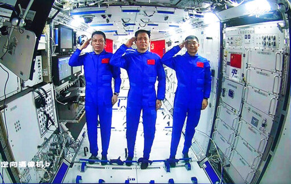 Astronautas chineses, a partir da esquerda;  Tang Hongbo, Nie Haisheng e Liu Boming saúdam a bordo do módulo central da estação espacial chinesa Tianhe durante uma conversa por vídeo com o presidente chinês Xi Jinping, em 23 de junho de 2021.