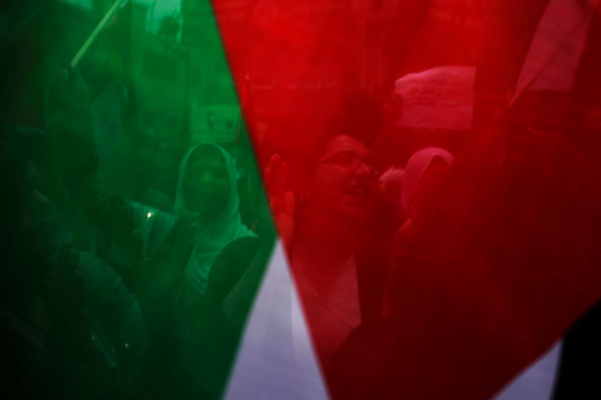 FILE- Palestinian women are seen through the Palestinian flag as they take part in a rally celebrating the signing of a reconciliation agreement between Fatah and Hamas, in the West Bank city of Ramallah, Wednesday, May 4, 2011.