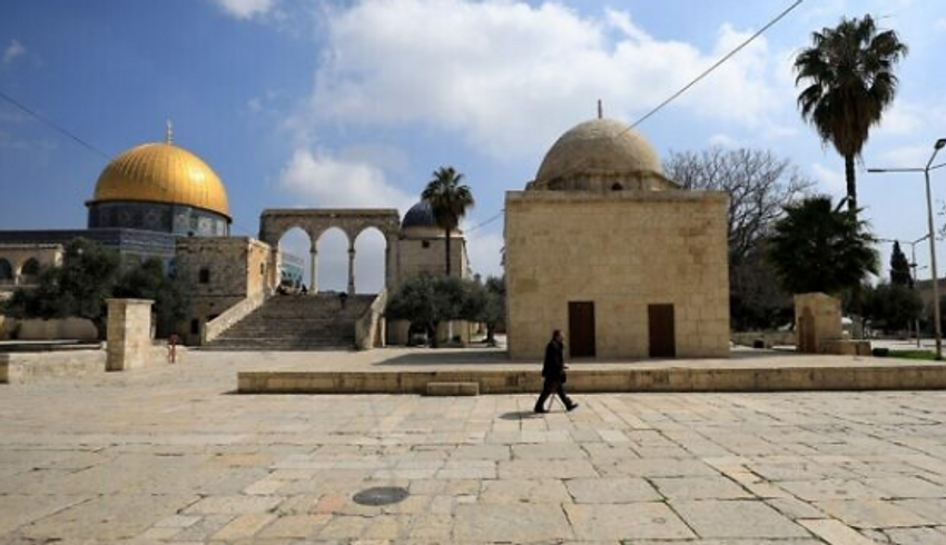 Um homem passa pela Cúpula da Rocha (à esquerda) dentro do complexo do Monte do Templo na Cidade Velha de Jerusalém, em 16 de março de 2020.